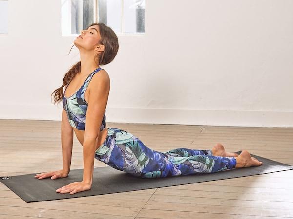 Žena cvičící na podložce jógu