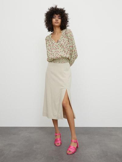 Žena v krémové midi sukni s postranním rozparkem