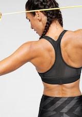 Cvičící žena ve sportovní podprsence s racerback ramínky