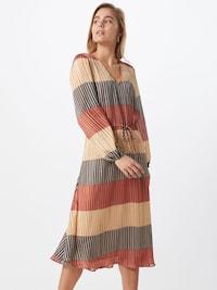Žena v elegantných voľných letných šatách s pásikmi