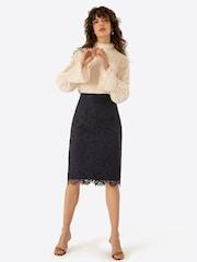 Žena v elegantní černé krajkové midi sukni