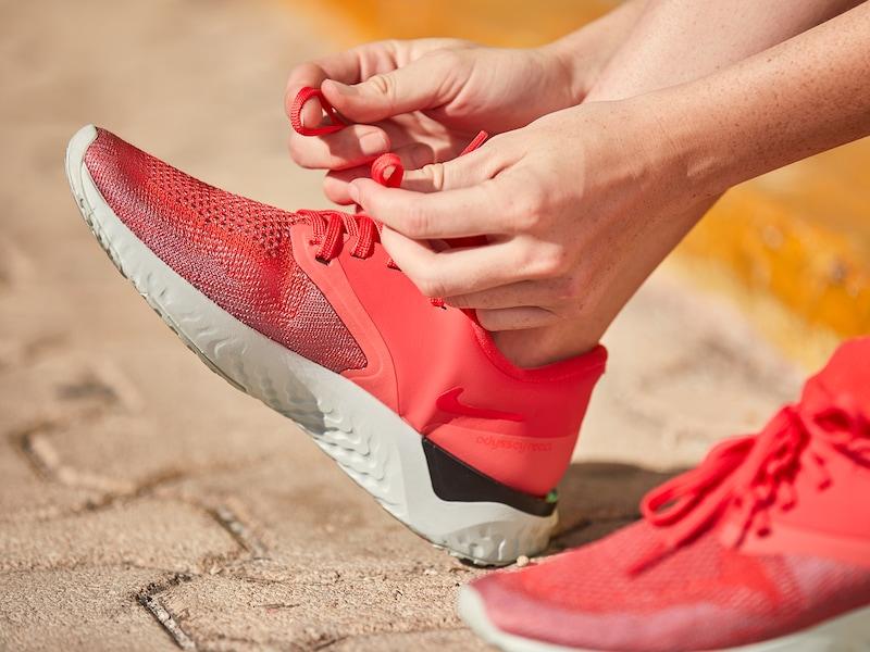 Frau zieht sich rote Laufschuhe an