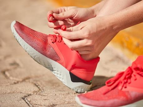Vrouw trekt rode hardloopschoenen aan