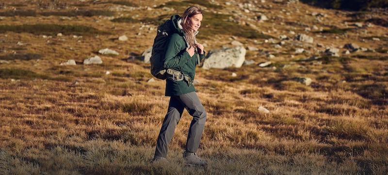 Frau wandert mit Outdoor-Ausrüstung durch die Natur