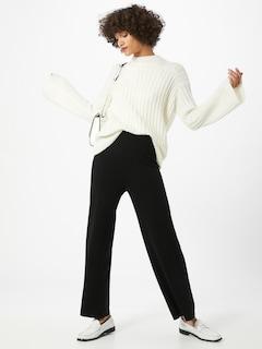 Žena v černých volných kalhotech značky Gestuz