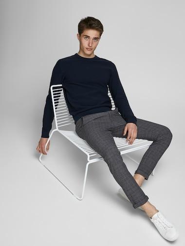 Muž sedící na židli oblečený v károvaných chino kalhotách