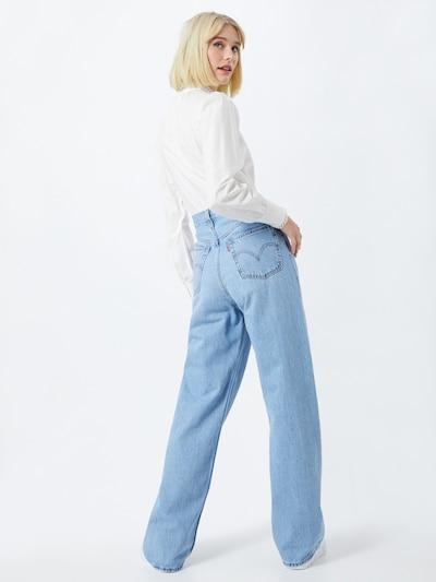 Eine Frau in weit geschnittenen Levi's Jeans