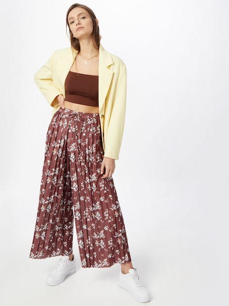 Žena u crvenim harem hlačama s cvijetnim uzorkom