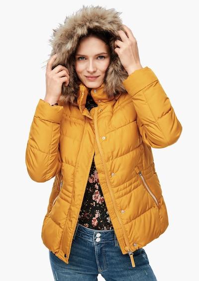 Žena v horčicové zimní bundě s kožešinovým límcem od značky QS